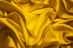 Silk Fabric Background, Yellow Satin Cloth Waves, Waving Textile royalty free stock images