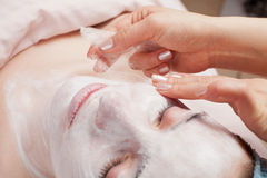 Silk facial mask applying, beauty treatment Royalty Free Stock Images