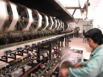 Silk Factory. Wheels spinning and workers manufacturing silk in a Xian, China silk factory Royalty Free Stock Photos
