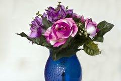 Silk flowers. A blue vase containing various silk flowers Royalty Free Stock Photos