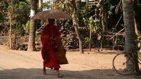 SILK ISLAND, CAMBODIA - MARCH 2014: buddhist monk walking. On countryside holding umbrella stock video footage