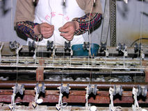 Silk manufacturing. Machine with silk threads in the foreground and a woman in the background threading the machine Stock Image
