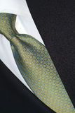 Silk necktie and dark suit. Blue and yellow silk necktie, white shirt and dark suit Royalty Free Stock Photography