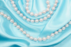 Silk and pear necklace. Blue silk background and pearl necklace Stock Photo