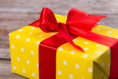 Silk red ribbon on a yellow gift. Royalty Free Stock Images