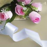 Silk ribbon, pink rose on yellow background. stock photo