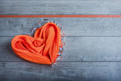 Silk scarf in the form of heart. Wedding or valentine's gift orange silk scarf is laid in the shape of a heart on a gray wooden background stock images