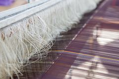 Silk string in weaving matchine tomake craftmanship. Close up silk string in weaving matchine tomake craftmanship textile in Thai traditional style royalty free stock image
