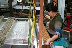 Silk Weaving. Woman weaving silk cloth in Thailand royalty free stock image