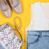 Silk white top, denim shorts, nude shoes, purse on a bright background. Stylish female summer clothing collection overhead on a bright yellow background Stock Photography