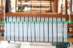 Silke som väver på en handvävstol Arkivfoton
