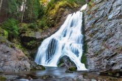 Silkeslen vit vattenfall djupt i bergen arkivbild