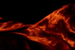 Silky textile on black background. Warm color Royalty Free Stock Images