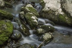 Silky Water falling over Moss Covered Rocks royalty free stock photos