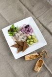 Sill med unga potatisar, lökar och rostade bröd Arkivfoto