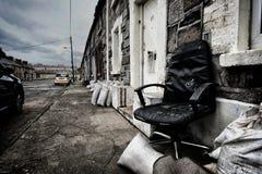 Silla abandonada en fila de casas Imagenes de archivo
