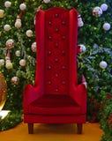 Silla alta grande para Santa Claus con el árbol de navidad verde en el fondo fotografía de archivo