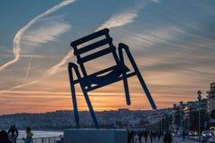 Silla azul: Puesta del sol en Niza, francesa riviera fotos de archivo