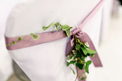 Silla blanca adornada con la cinta y el verdor violetas sobre él Fotografía de archivo