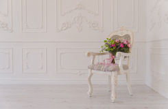 Silla blanca con el bouqet de la flor staing en la esquina del estudio Fotos de archivo