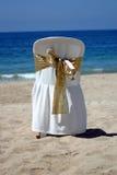 Silla blanca con la cinta del oro para una boda de playa Fotografía de archivo