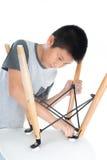 Silla blanca de la reparación asiática del muchacho aislada en blanco Fotos de archivo