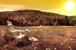Silla blanca del adirondack en un campo en la puesta del sol Fotografía de archivo libre de regalías