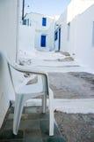 Silla blanca en una calle griega clásica de la isla imagenes de archivo