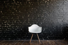 Silla blanca que se coloca en sitio en piso de madera marrón sobre la pared de ladrillo negra Imágenes de archivo libres de regalías