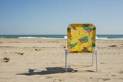 Silla colorida del verano de los niños aislada en la playa en un día claro Imagen de archivo