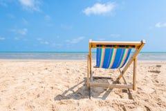 Silla colorida en la playa arenosa el día soleado que busca el azul foto de archivo