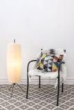 Silla con el amortiguador brillante y la lámpara de pie elegante Imagenes de archivo