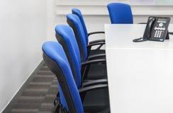 Silla con el teléfono del IP en la mesa de reuniones blanca en oficina Imágenes de archivo libres de regalías