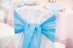Silla con la cinta y arco en restaurante boda Fotografía de archivo libre de regalías