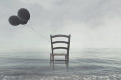 silla con los globos negros atados a la orilla del océano Fotografía de archivo