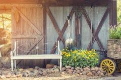 Silla con los utensilios de jardinería en la granja del vintage de la luz del sol, vintage fi Imagen de archivo libre de regalías