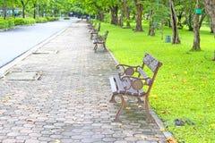 Silla de acero en la acera en el parque con la hierba verde Fotografía de archivo