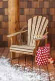 Silla de Adirondack con los regalos de la Navidad en la cubierta de madera nevosa del pórtico de una cabina rústica del país Casa imagen de archivo libre de regalías