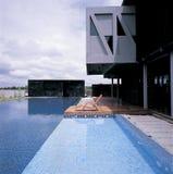 Silla de cubierta en el escritorio de madera al lado de la piscina fotos de archivo libres de regalías