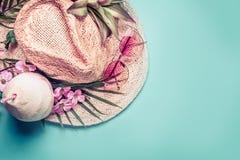 Silla de cubierta en la playa en Brighton Accesorios de la playa: sombrero de paja, hojas de palma, vidrios de sol rosados, flore Foto de archivo