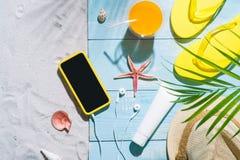 Silla de cubierta en la playa en Brighton Chancletas amarillas, sombrero de paja, zumo de naranja y m Foto de archivo libre de regalías