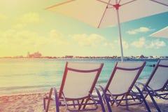Silla de cubierta en una playa hermosa durante salida del sol Imagen de archivo libre de regalías
