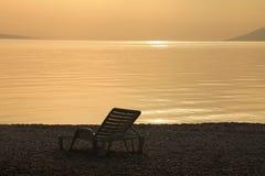 Silla de cubierta y puesta del sol hermosa Fotografía de archivo libre de regalías