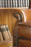 Silla de cuero vieja y estante para libros de madera Imagen de archivo