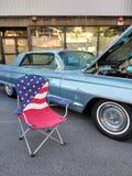Silla de jardín de la bandera americana cerca de un coche clásico en un Car Show Imágenes de archivo libres de regalías