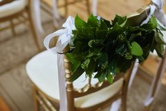 Silla de madera adornada con las hojas del verde y las rayas blancas para la ceremonia de boda Imágenes de archivo libres de regalías