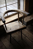 Silla de madera antigua en una ventana Fotografía de archivo libre de regalías