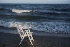 Silla de madera blanca en la playa Playa vacía, puesta del sol, tiempo frío y el mar Fotos de archivo