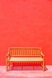 Silla de madera de la calle sobre la pared roja Fotos de archivo