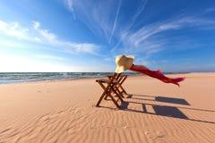 Silla de madera en la playa con Straw Hat y la bufanda imagen de archivo